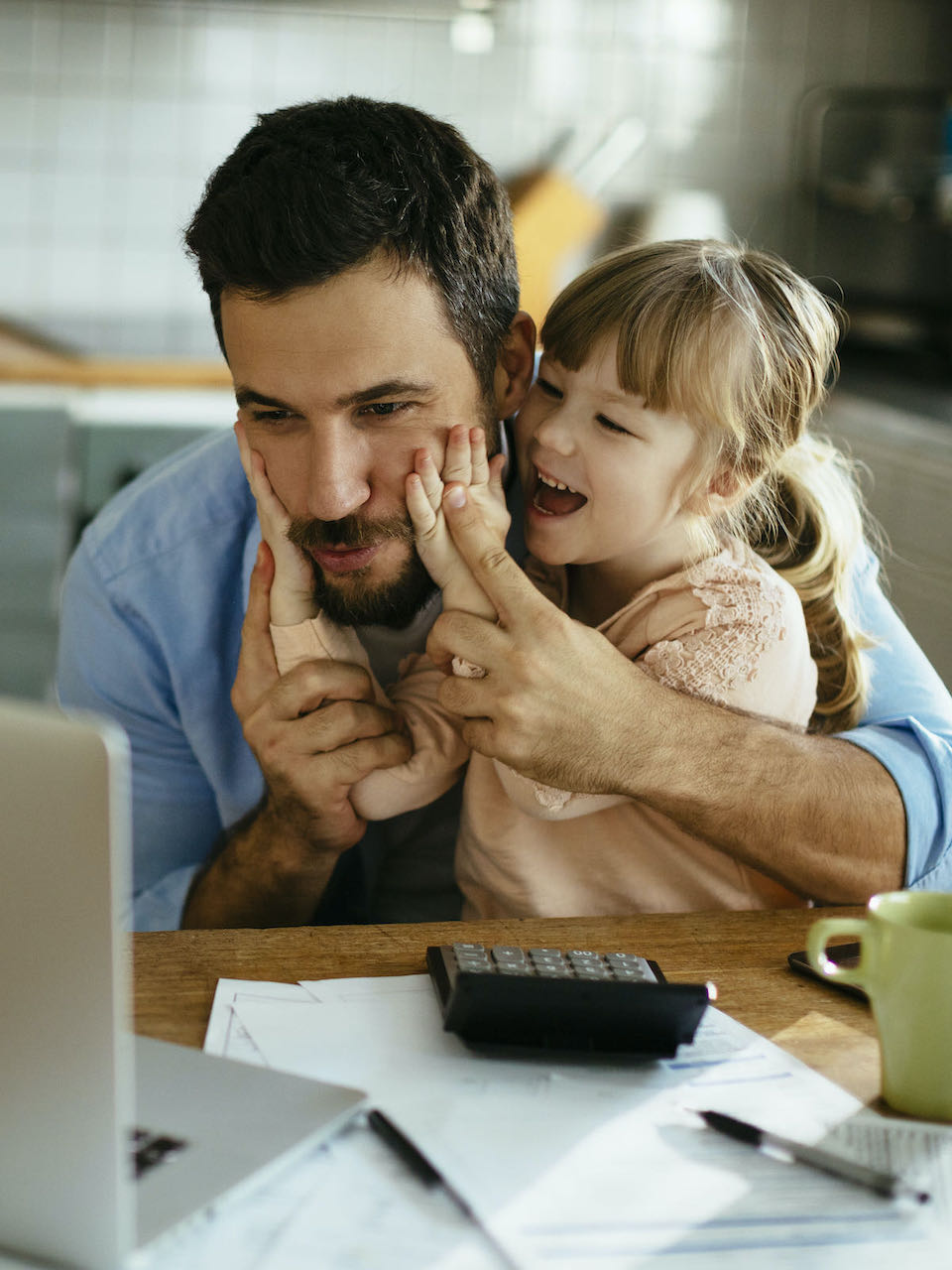 Photo of man and daughter making faces at computer