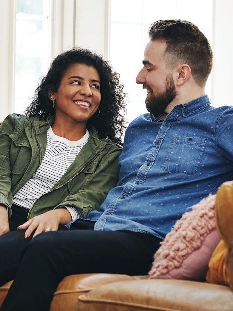 Photo of young couple laughing together in home